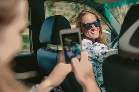 time drive: Happy young woman ready to drive car looking to her friend while she taking photo with a smartphone. Female friendship and leisure time concept.