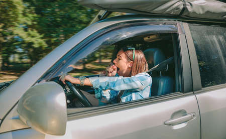 Portrait of tired young woman driving car and yawning after too long travel. Risk and danger at the road concept.