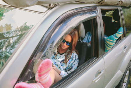 open windows: Young women resting with her legs over a open window car. Travel and relax time concept.