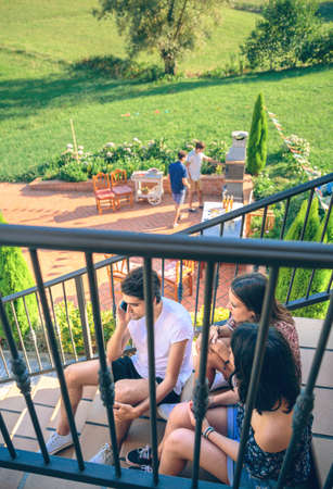 cellular: Young man calling by phone sitting on the home stairs with his friends over a summer barbecue background. Young people lifestyle concept.