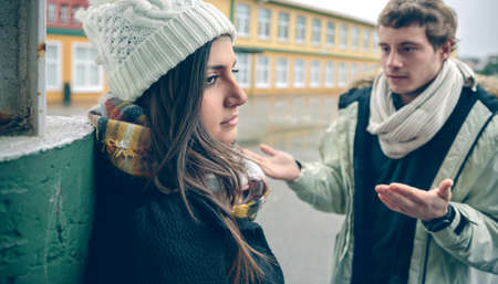 autumn rain: Close up of displeased woman listening arguments of young man during a hard quarrel outdoors. Couple relationships and problems concept. Stock Photo