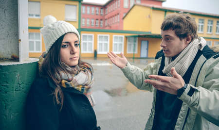 arguments: Portrait of displeased woman listening arguments of young man during a hard quarrel outdoors. Couple relationships and problems concept.