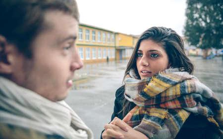 pardon: Portrait de jeune femme demandant des excuses à l'homme offensé après une dispute dur extérieur. Couple relations et les problèmes concept.