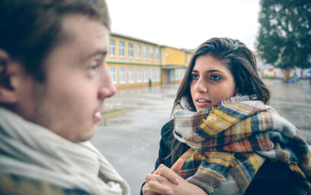 apologize: Portrait of young woman asking apologize to offended man after a hard quarrel outdoors. Couple relationships and problems concept.