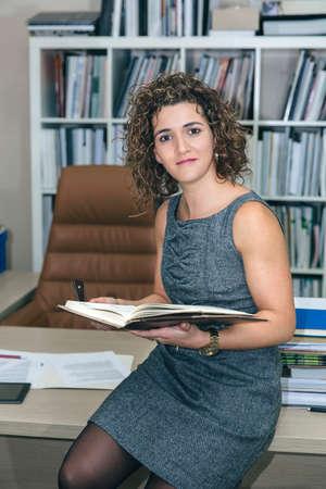 expresiones faciales: Retrato de negocios la celebración de cuaderno que se sienta sobre la mesa de escritorio en la oficina y mirando a la cámara Foto de archivo