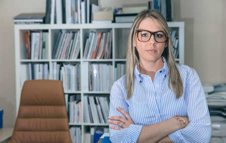 expresiones faciales: Retrato de mujer de negocios con gafas de pie en la oficina contra de estantería Foto de archivo