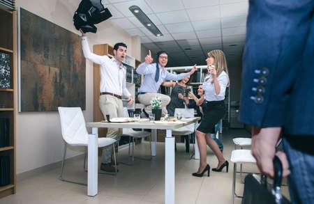 Nahaufnahme von Hand Chef mit Aktenkoffer ins Büro ankommen, während seine Arbeiter in einer großen Party tanzen und trinken Standard-Bild