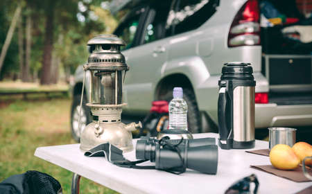 Oil lamp, thermos and binoculars over camping table in the forest with  offroad vehicle in the background