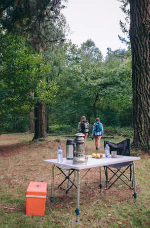 foreground focus: Back view of two unrecognizable women hiking in the forest with camping table in the foreground. Focus on people.
