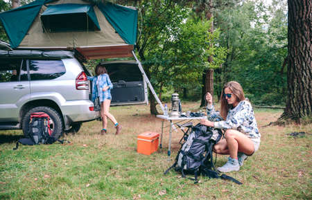 holiday trip: Young woman preparing backpack for a hiking trip whit her friend searching equipment inside of their vehicle Stock Photo