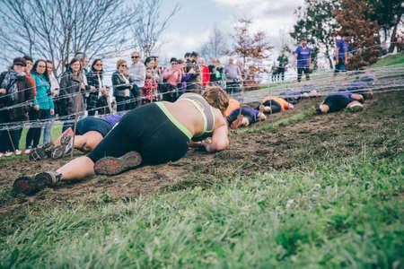 GIJON, ESPAÑA - 31 de enero, 2016: Los corredores en la carrera farinato, una carrera de obstáculos extrema, celebrado en Gijón, España, el 31 de enero de 2016. Vista posterior de la mujer de arrastrarse por debajo de un alambre de púas en la carrera.