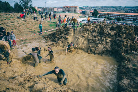 mud pit: GIJON, SPAIN - JANUARY 31, 2016: Runners into the Farinato Race event, a extreme obstacle race, celebrated in Gijon, Spain, on January 31, 2016. Participants crossing a mud pit in a test of the race.