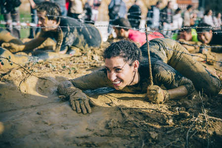 GIJON, SPAIN - JANUARY 31, 2016: Runners into the Farinato Race, a extreme obstacle race, celebrated in Gijon, Spain, on January 31, 2016. Woman crawling under a barbed wire in a test of the race. 에디토리얼