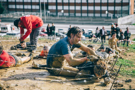 participant: GIJON, SPAIN - JANUARY 31, 2016: The Farinato Race, a extreme obstacle race, celebrated in Gijon, Spain, on January 31, 2016. Participant helping to woman crawling under a barbed wire in the race. Editorial