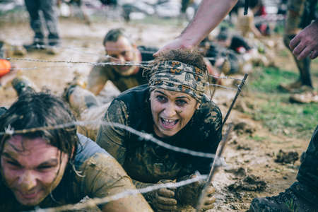GIJON, SPAIN - JANUARY 31, 2016: The Farinato Race, a extreme obstacle race, celebrated in Gijon, Spain, on January 31, 2016. Senior woman crawling under a barbed wire in a test of the race.
