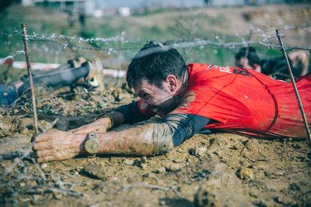 GIJON, ESPAÑA - 31 de enero, 2016: La carrera farinato, una carrera de obstáculos extrema, celebrado en Gijón, España, el 31 de enero de 2016. Retrato de corredor arrastrarse por debajo de un alambre de púas en una prueba de la carrera.