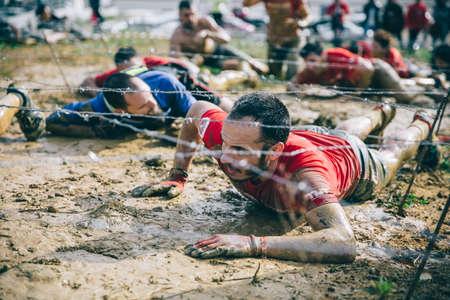 GIJON, ESPAÑA - 31 de enero, 2016: La carrera farinato, una carrera de obstáculos extrema, celebrado en Gijón, España, el 31 de enero de 2016. Retrato de corredor arrastrarse por debajo de un alambre de púas en una prueba de la carrera. Editorial