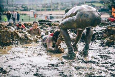 GIJON, ESPAÑA - 31 de enero, 2016: La carrera farinato, una carrera de obstáculos extrema, que se celebra en Gijón, España, el 31 de enero de 2016. Hombre sucio ayudar a la mujer a arrastrarse por debajo de un alambre de púas en la carrera.