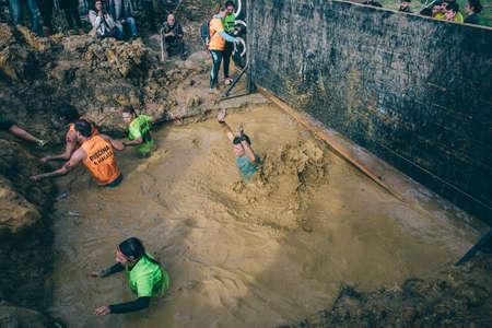 GIJON, ESPAÑA - 31 de enero, 2016: Los corredores en el evento de carrera farinato, una carrera de obstáculos extrema, celebrado en Gijón, España, el 31 de enero de 2016. Los participantes que cruzan un pozo de barro en una prueba de la carrera. Editorial
