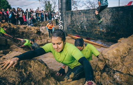 GIJON, SPAIN - JANUARY 31, 2016: Runners into the Farinato Race, a extreme obstacle race, celebrated in Gijon, Spain, on January 31, 2016. Portrait of woman crossing a mud pit in a test of the race.