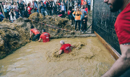 GIJON, SPAIN - JANUARY 31, 2016: Runners into the Farinato Race event, a extreme obstacle race, celebrated in Gijon, Spain, on January 31, 2016. Participants crossing a mud pit in a test of the race.