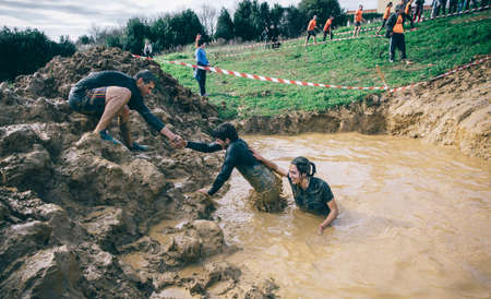 GIJON, SPAIN - JANUARY 31, 2016: Runners into the Farinato Race event, a extreme obstacle race, celebrated in Gijon, Spain, on January 31, 2016. Team helping to cross a mud pit in a test of the race.