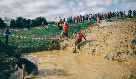 mud pit: GIJON, SPAIN - JANUARY 31, 2016: Runners into the Farinato Race event, a extreme obstacle race, celebrated in Gijon, Spain, on January 31, 2016. Man jumping to mud pit in a test of the race.