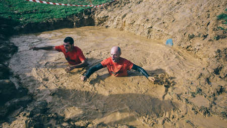 mud pit: GIJON, SPAIN - JANUARY 31, 2016: Runners into the Farinato Race event, a extreme obstacle race, celebrated in Gijon, Spain, on January 31, 2016. Men crossing a mud pit in a test of the race.