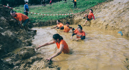 mud pit: GIJON, SPAIN - JANUARY 31, 2016: Runners into the Farinato Race event, a extreme obstacle race, celebrated in Gijon, Spain, on January 31, 2016. Team crossing a mud pit in a test of the race.