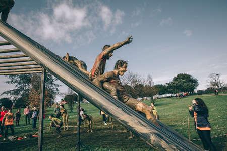 GIJON, ESPAÑA - 31 de enero, 2016: Los corredores en la carrera farinato, una carrera de obstáculos extrema, celebrado en Gijón, España, el 31 de enero de 2016. Los hombres felices bajando estructura metálica en la carrera.