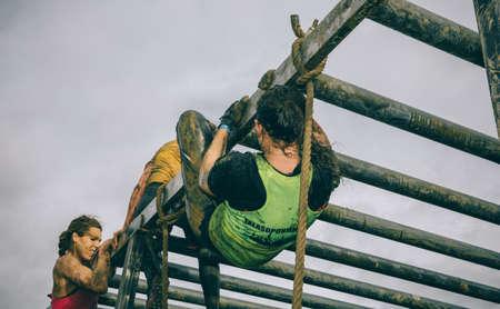 GIJON, ESPAÑA - 31 de enero, 2016: Los corredores en la carrera farinato, una carrera de obstáculos extrema, celebrado en Gijón, España, el 31 de enero de 2016. Mujeres que suben estructura metálica en una prueba de la carrera.