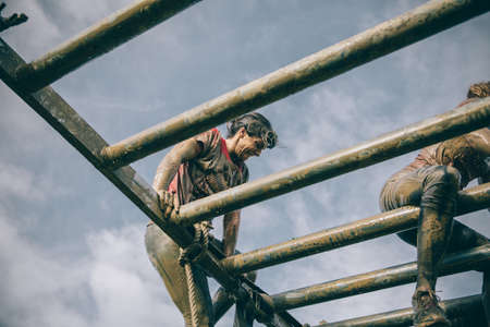 GIJON, SPAIN - JANUARY 31, 2016: Runners into the Farinato Race, a extreme obstacle race, celebrated in Gijon, Spain, on January 31, 2016. Dirty woman climbing metallic structure in test of the race.