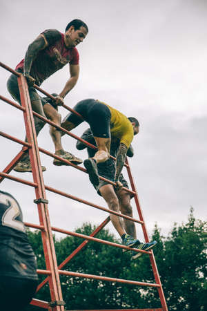 Gijón, España - 31 de enero de 2016: Los corredores en la carrera farinato, una carrera de obstáculos extrema, celebrado en Gijón, España, el 31 de enero de 2016. Los participantes de escalada estructura metálica en la carrera.