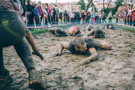 Gijón, España - 31 de enero de 2016: Los corredores en la carrera farinato, una carrera de obstáculos extrema, celebrado en Gijón, España, el 31 de enero de 2016. El hombre arrastrarse por debajo de una malla electrificada en una prueba de la carrera. Editorial