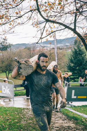 dirty man: Gijon, Spain - January 31, 2016: Runners into the Farinato Race, a extreme obstacle race, celebrated in Gijon, Spain, on January 31, 2016. Dirty man carrying wooden logs in a test of the race.