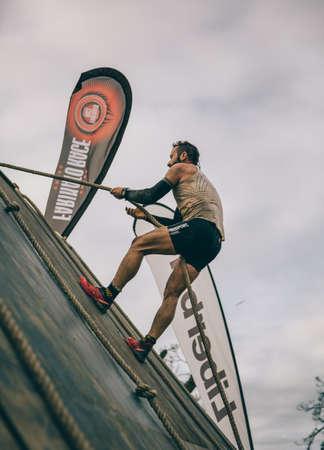 Gijón, España - 31 de enero de 2016: Corredor en la carrera farinato, una carrera de obstáculos extrema, celebrado en Gijón, España, el 31 de enero de 2016. Hombre que sube una pared de madera con una cuerda en una prueba de la carrera.