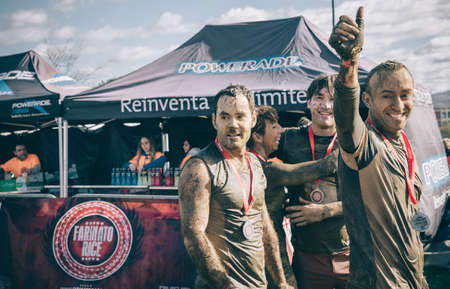Gijon, Spain - January 31, 2016: Runners into the Farinato Race, a extreme obstacle race, celebrated in Gijon, Spain, on January 31, 2016. Happy team with medals celebrating their victory in the race.