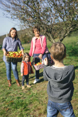 electronic tablet: Back view of cute boy taking a photo with electronic tablet to family with fresh organic apples in a wicker basket after harvest. Family leisure time concept.