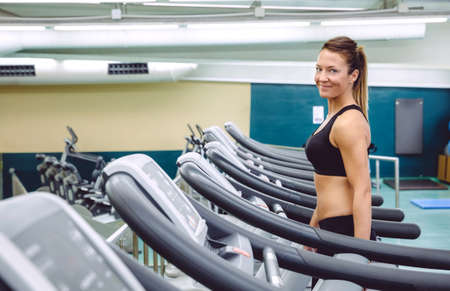warming up: Portrait of smiling woman warming up over treadmill in a training session on fitness center