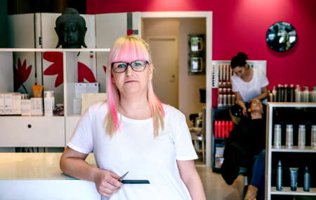 parlour: Portrait of smiling woman hairdresser standing in a hair and beauty salon with employee washing woman hair in the background Stock Photo