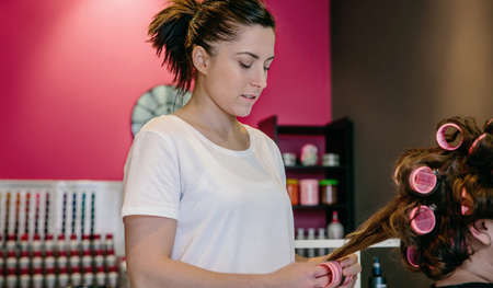 horizontal haircut: Portrait of woman hairdresser curling hair to customer with curlers in a hair and beauty salon Stock Photo