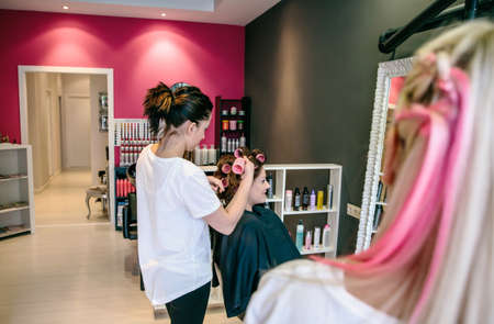 entrepeneur: Hairdresser curling woman hair with curlers in a hair and beauty salon Stock Photo