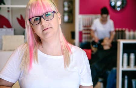 Beleza: Retrato da mulher cabeleireiro pé em um salão de cabeleireiro e beleza com cabelo lavagem da mulher do trabalhador no fundo