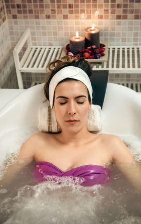 hydrotherapy: Portrait of young beautiful woman with turban lying in tub doing hydrotherapy treatment. Health and beauty concept.