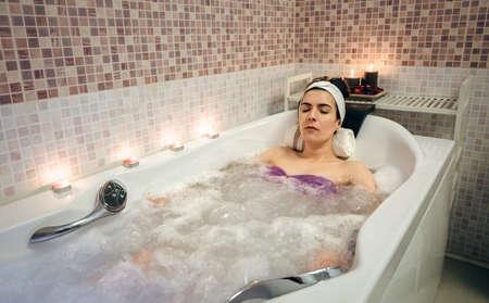 Giovane bella donna con il turbante che giace in vasca fa il trattamento di idroterapia. Salute e concetto di bellezza. Archivio Fotografico - 52549208