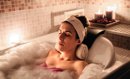 beauty eyes: Portrait of young beautiful woman with turban lying in tub doing hydrotherapy treatment. Health and beauty concept.
