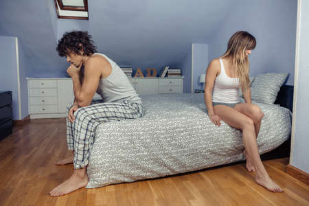 Portrait of angry young couple sitting over bed back to back after a hard quarrel. Couple relationship and problems concept.