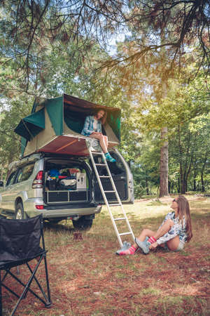 shoes off: Young happy woman resting in a tent over car while other woman putting hiking boots sitting on the grass Stock Photo