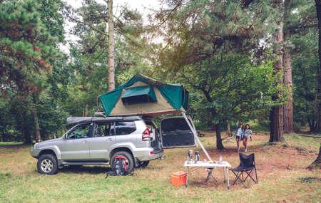 mochila de viaje: lámpara de aceite y termo sobre la mesa de camping en un camping con dos mujeres que llegan de senderismo en el fondo Foto de archivo