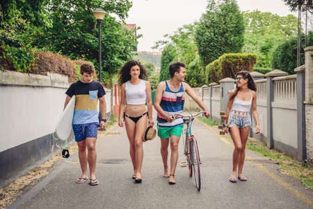 people together: Happy young people in summer clothes walking along road while holding surfboard, skateboard and bicycle. Summer lifestyle concept.